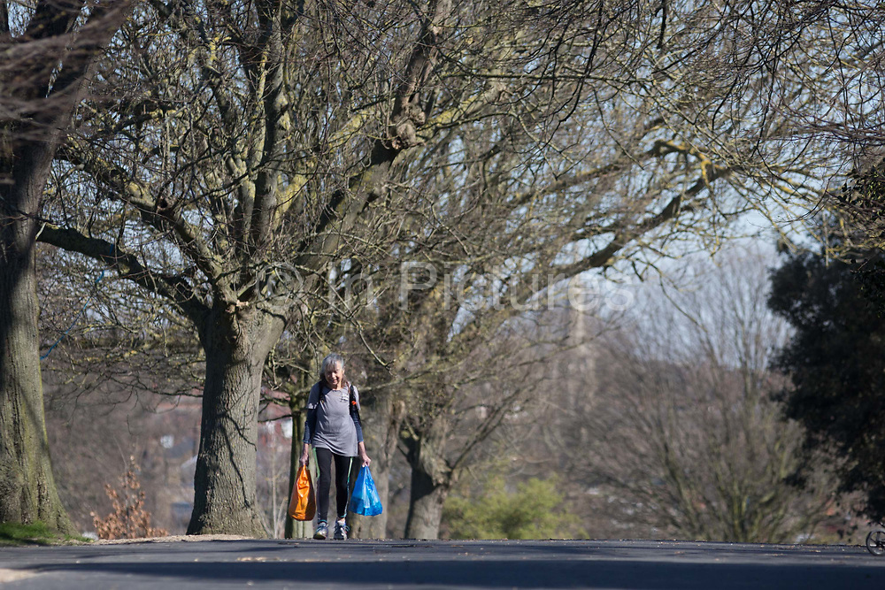 As the UK government considers further restrictions of movement in public places during the Coronavirus pandemic, and the elderly and vulnerable are being given preferential access to supermarkets and shops, an elderly lady carries shopping bags through Brockwell Park in Herne Hill, on 23rd March 2020, in London, England.