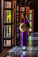 Vietnamese women wearing the traditional Ao Dai costume walking in the Imperial City, a walled palace within the citadel of the city of Huế which is the former imperial capital of Vietnam. Hue, Central Vietnam.