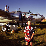 Known as 'Old Glory', a polished silver Boeing Mitchell B-25 is refuelled in readiness for a display flight at Oshkosh Air Venture, the world's largest air show in Wisconsin USA. In afternoon light, a lady in a stars and stripes shirt stands arms behind her back admiring the lovingly restored polished twin-engine bomber, the most heavily armed airplane of the second world war used for high and low-level bombing, strafing, photoreconnaissance, submarine patrol and fighter. Close to a million populate the mass fly-in over the week, a pilgrimage worshipping all aspects of flight. The event annually generates $85 million in revenue over a 25 mile radius from Oshkosh. Picture from the 'Plane Pictures' project, a celebration of aviation aesthetics and flying culture, 100 years after the Wright brothers first 12 seconds/120 feet powered flight at Kitty Hawk,1903