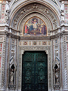 The main portal doors from the Basilica di Santa Maria del Fiore, (more commonly called the 'Duomo'). Florence, Italy. Three huge bronze doors, adorned with scenes from the life of Madonna. They date from 1899 to 1903. Around the doors are multiple works of art: Mosaics by Niccolò Barabino, a half-relief by Tito Sarrocchi, and a series of niches and busts. The duomo was started in 1296 based on Arnolfo di Cambio's design, but was not complete until 1436 when Filippo Brunelleschi engineered the dome. One of Italy's largest churches.
