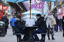 © Licensed to London News Pictures. 15/12/2020. London, UK. Visitors to Carnaby Street enjoy an outdoor beer in London's West End. London and other areas of the south east are to enter tier three restrictions at midnight tonight as Covid-19 infection rates rise. Photo credit: Peter Macdiarmid/LNP