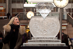 © Licensed to London News Pictures. 12/01/2012. London, UK. A woman admires the giant Jubilee diamond made from ice in Canary Wharf's Reuters Plaza which was sculpted by Asanga Amerasinghe to celebrate the Queen's diamond jubilee this year in advance of the London Ice Sculpting festival which starts tomorrow (13/01). Photo credit : James Gourley/LNP