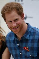 Prince Harry wears a specially made red brooch from a member of the Joyful Noise choir, a group from NAZ, a sexual health charity for minority communities, at The Hurlingham club in London.