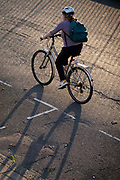 A cyclist pedals down a residential road, the bike's shadow falling onto the road surface, on 21st September 2021, in London, England.