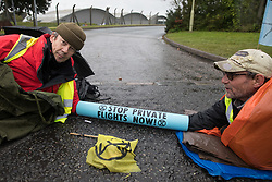 Extinction Rebellion climate activists lie in the road locked together using an arm tube to block an entrance to Farnborough Airport on 2nd October 2021 in Farnborough, United Kingdom. Activists blocked three entrances to the private airport to highlight elevated carbon dioxide levels produced by super-rich passengers using private jets and 'greenwashing' by the airport in announcing a switch to sustainable aviation fuel (SAF).