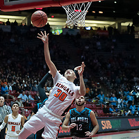 """Gallup Bengals Joaquin Ortega (30) gets the layup off as a  Del Norte Knights defender is on his back during the NMAA State Tournament. The Knights defeated the Bengals 55-49 at """"The Pit"""" in Albuquerque Wednesday evening."""