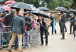 Prince Harry takes a bouquet of flowers from a wellwisher to add to the tributes to Diana, Princess of Wales attached to the Golden Gates of Kensington Palace, London, ahead of the 20th anniversary of his mother's death.
