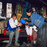 Namdu Sherpa pours chang for Gordon Wiltsie at the Khumbu Lodge in Namche Bazar in the Khumbu region of Nepal 1986.