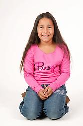 Young girl kneeling; smiling,