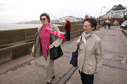 Two elderly women walking by the sea,
