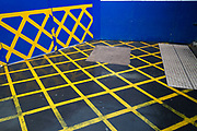 Yellow warning tape is placed on a blue wall at Whitechapel station while refurbishment is underway to improve the station in London, England, United Kingdom. The grid pattern it creates causes an graphic visual patchwork squares and diamond shapes.