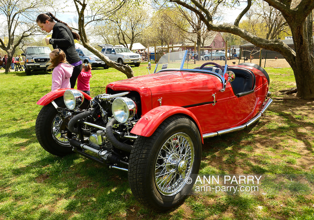 Floral Park, New York, U.S. - April 27, 2014 - A family with young children looks at a red BRA CX3, a custom Beribo Replica Automobiles kit vehicle with three wheels, and registered by DMV as a 2009 Custom Motorcycle, is exhibited at the 35th Annual Antique Auto Show at Queens Farm.
