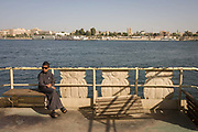 A young middle-class boy sits on the top deck of the state-run ferry across the River Nile at Luxor, Nile Valley, Egypt. Plying the great African river is a cheap fare state-run ferry used by commuters and schoolboys use this ferry to and from school.