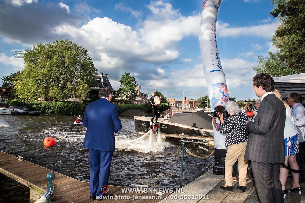 NLD/Amsterdam/20140612 - Hilton Haringparty 2014, Eerste vaatje Hollandse nieuwe haring word door flyboarder overhandigt aan general manager Roberto Prayer