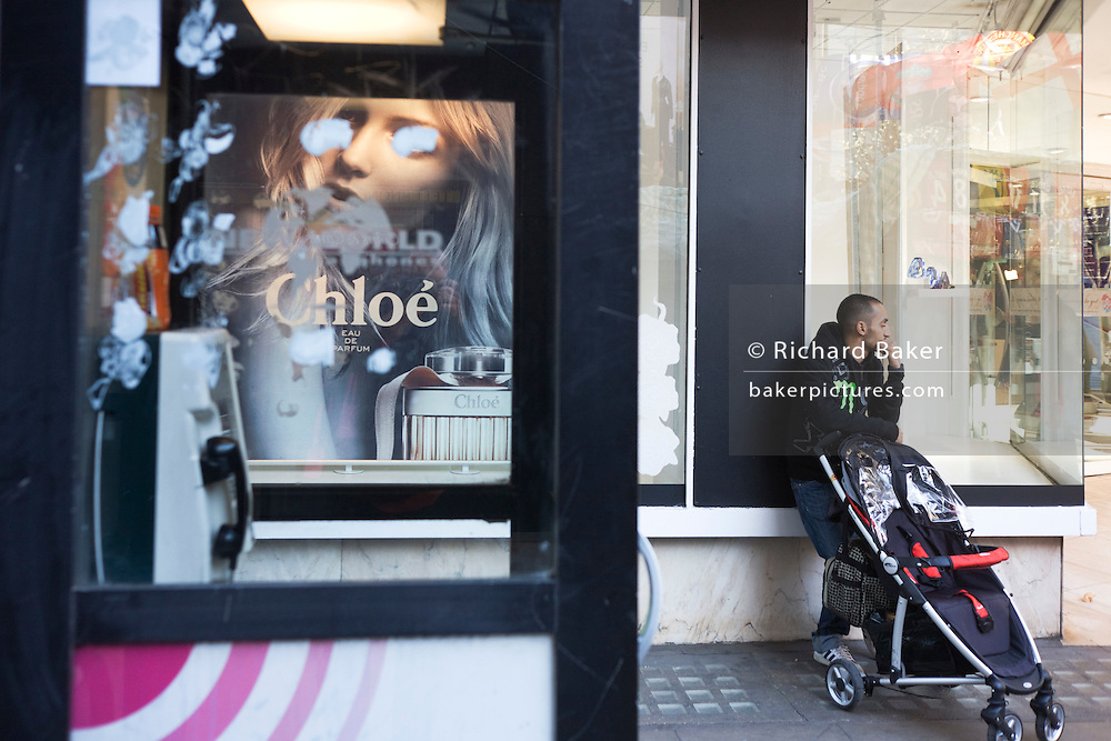 The eyes of an ad model are obscured by daubs of paint on a phone kiosk window as a dad awaits his partner.