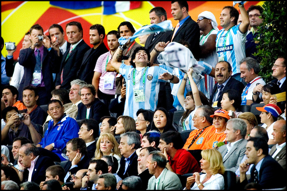 Germany, Frankfurt, 21-06-2006.<br /> World Cup Football.<br /> Diego Armando Maradona screams like an idiot and waves with an Argentine national shirt towards the Argentine supporters box during the match Netherlands versus Argentina.<br /> Below on the right side are Johan Cruijff and his wife Danny watching the game..<br /> Photo: Klaas Jan van der Weij
