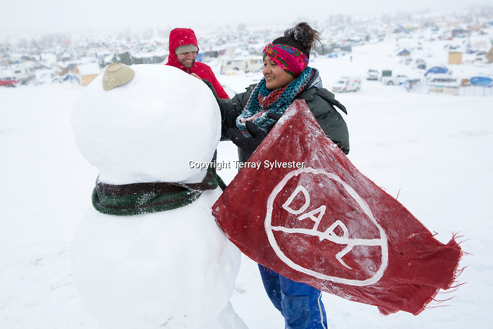 Mikaela Jackson (right) from Carson City, Nevada, builds a snowman during a snowstorm in the opposition camp against the Dakota Access oil pipeline on November 28, 2016. Cannon Ball, North Dakota, United States.