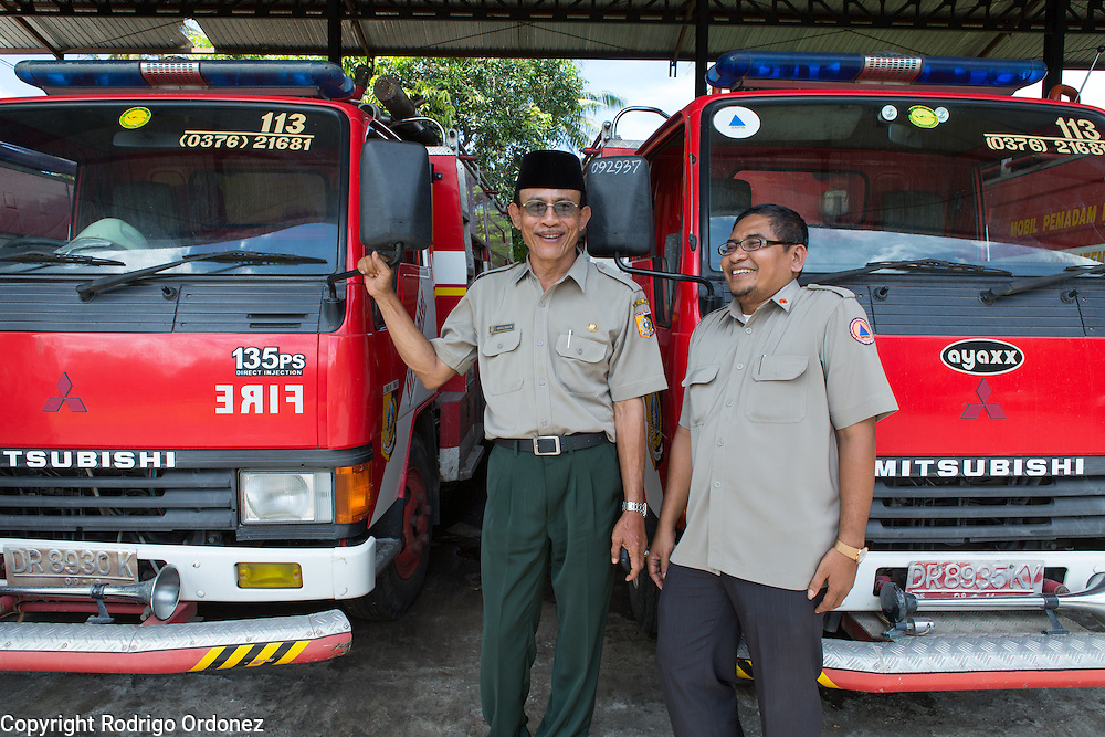 Government officials of the Regional Disaster Management Agency (BPBD in Indonesian) pose for a photograph with fire engines in their office in Selong, East Lombok district, West Nusa Tenggara province, Indonesia. In the image are (from left to right) Abdul Hakim, Head of the Regional Disaster Management Agency in East Lombok; and Supriadi, Head of Subdivision.