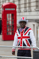 © Licensed to London News Pictures . 17/04/2013 . London , UK . A colourfully dressed man in Union Jack hat and jacket waits for the funeral procession at the foot of Whitehall . The funeral of former British Conservative Prime Minister , Baroness Margaret Thatcher , today (Wednesday 17th April 2013) in Central London . Baroness Thatcher died from a stroke at the age of 87 . Photo credit : Joel Goodman/LNP