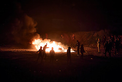 © Licensed to London News Pictures. 23/10/2016. Calais, France. A group of migrants stand around burning remains as they clash with French police on the eve of the demolition of the camp. French authorities have given an eviction order to thousands of refugees and migrants living at the makeshift living area of the French coast. Photo credit: Ben Cawthra/LNP