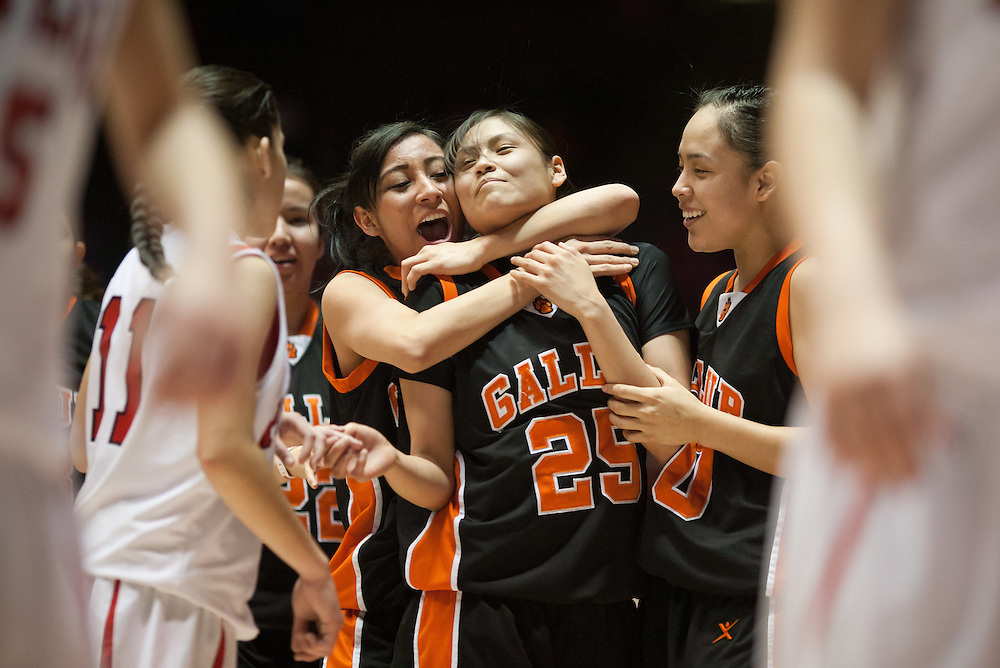 Stacey Charley is hugged while walking off the court by teammates Celia Herrera (Left) and Robyn Antone (Right) after Gallup defeated Roswell 50-44 in the AAAA semifinals Thursday morning in Albuquerque at The Pit.