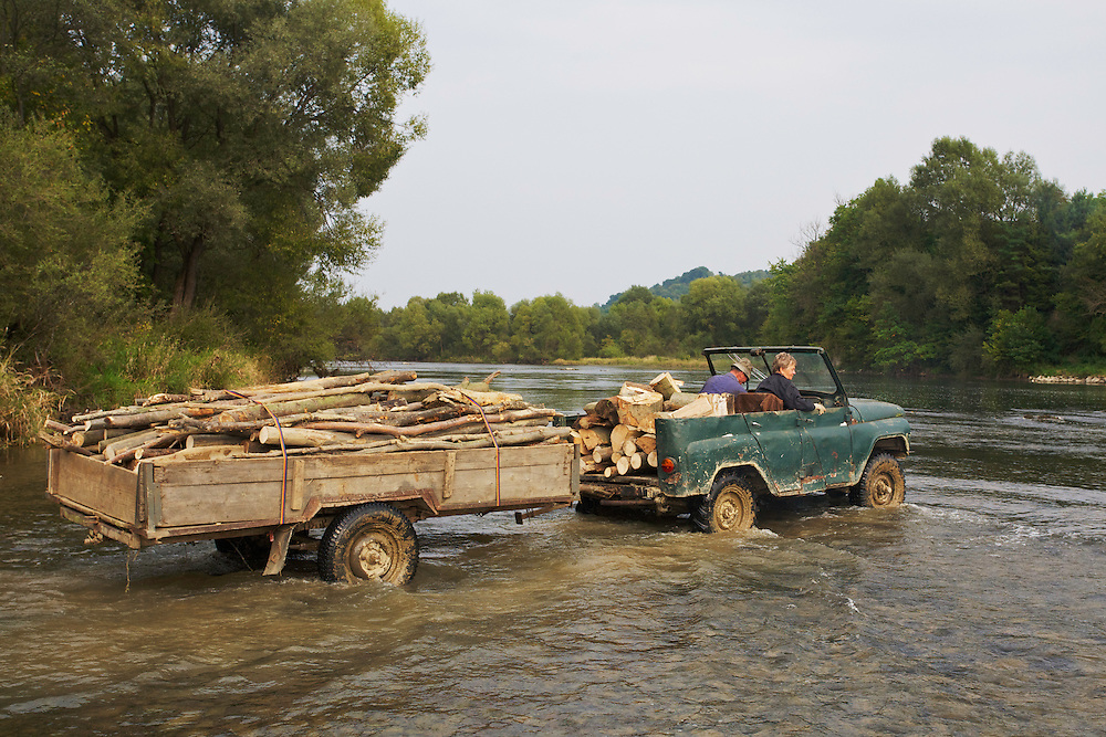Old couple transporting logs through the San River to their home village Bachlawa. Poland.