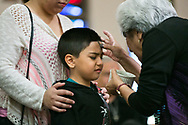 Joseph Stickfort, 6, reacts as ashes are placed on his head by Elvia Rodriguez on Wednesday during mass at the Cathedral of the Immaculate Heart of Mary. Holding Stickfort is his mother Julie Stickfort.
