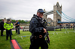 © Licensed to London News Pictures. 05/06/2017. London, UK. An armed police officer watches over during vigil at Potters Fields Park outside City Hall in London for those who lost their lives in the London Bridge terror attack. Three men attacked members of the public  after a white van rammed pedestrians on London Bridge. Ten people including the three suspected attackers were killed and 48 injured in the attack. Photo credit: Ben Cawthra/LNP