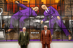 "© Licensed to London News Pictures. 12/04/2021. LONDON, UK.  Gilbert & George in front of ""Woken"", 2020, at their ""NEW NORMAL PICTURES"" exhibition at White Cube's Mason's Yard gallery in Mayfair. The exhibition displays 26 pictures from a new series the pair have been working on for over two years.  The UK government's coronavirus roadmap out of lockdown has allowed art galleries to reopen today. The exhibition runs 13 April to 8 May 2021.  Photo credit: Stephen Chung/LNP"