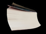 overhead view of a thick book against a black background