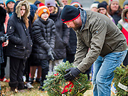 14 DECEMBER 2019 - DES MOINES, IOWA: A volunteer places a wreath to honor Navy veterans during the ceremony to mark the laying of Christmas wreaths on veterans' graves. Volunteers working with Wreaths Across America placed Christmas wreaths on the headstones of more than 600 US military veterans in Woodland Cemetery in Des Moines. The cemetery, one of the first in Des Moines, has the graves of veterans going back to the War of 1812.   PHOTO BY JACK KURTZ