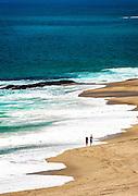 Couple Walking Along the Shoreline of Table Rock Beach In Laguna