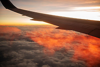 Airplane wing at sunrise flying over Brazil.
