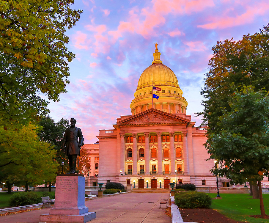 Wisconsin State Capitol, all aglow at dawn, Saturday, October 19, as venders at the Dane County Farmers' Market welcome customers. Photo taken October 19, 2019.