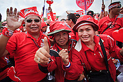 """26 MARCH 2009 -- BANGKOK, THAILAND: Supporters of exiled former Thai Prime Minister Thaksin Shinawatra demonstrate in favor of his return in Bangkok. More than 30,000 members of the United Front of Democracy Against Dictatorship (UDD), also known as the """"Red Shirts""""  and their supporters gathered on Sanam Luang (the vast open field in front of the Palace) and descended on central Bangkok March 26 to start a series of protests against and demand the resignation of current Thai Prime Minister Abhisit Vejjajiva and his government. The protest is a continuation of protests the Red Shirts have been holding across Thailand. Thaksin was deposed in a coup and went into exile rather than go to prison after being convicted on corruption charges. He is still enormously popular in rural Thailand.   PHOTO BY JACK KURTZ"""