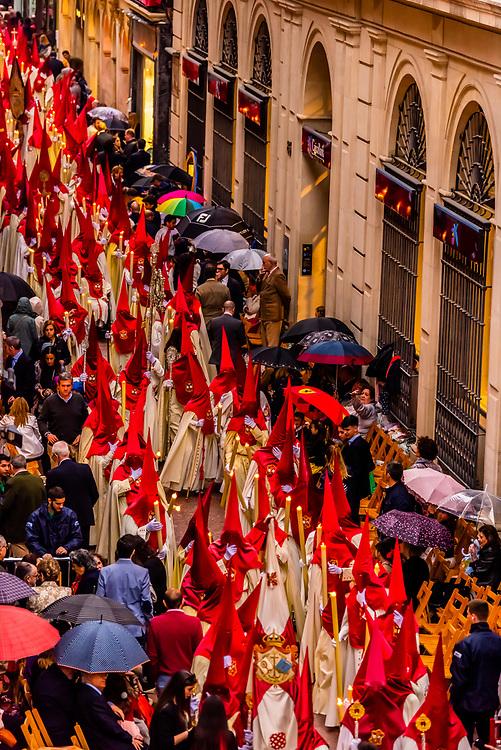 Hooded Penitents (Nazarenos) in the procession of the Brotherhood (Hermandad) La Lanzada, Holy Week (Semana Santa), Seville, Andalusia, Spain.