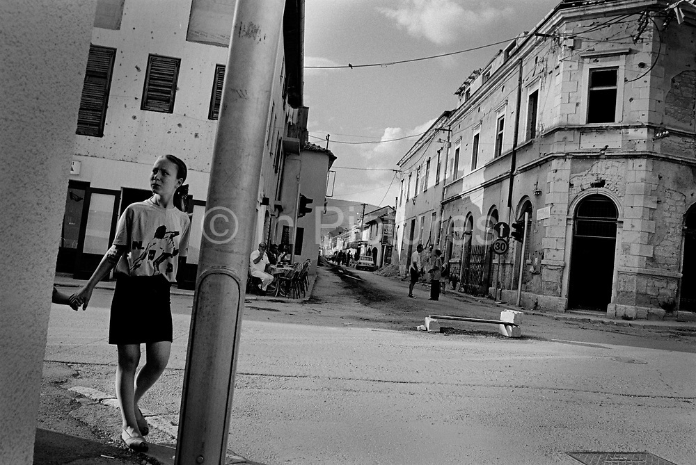 "Street life returns to normal after the end of the Muslim Croat war. It was destroyed by systemic bombardment from Croat guns during the Croat Muslim War, when the Croats endeavored to "" cleanse"" the town of non Croats. Mostar, Bosnia and Herzegovina."