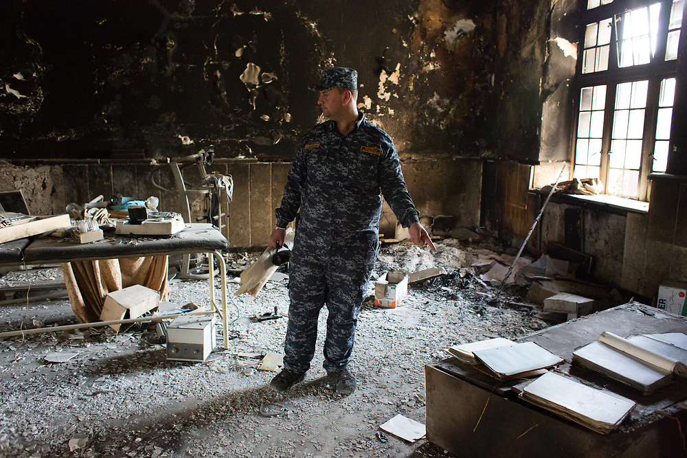 An Iraq Federal Police office check out the destruction of the Mosul museum.