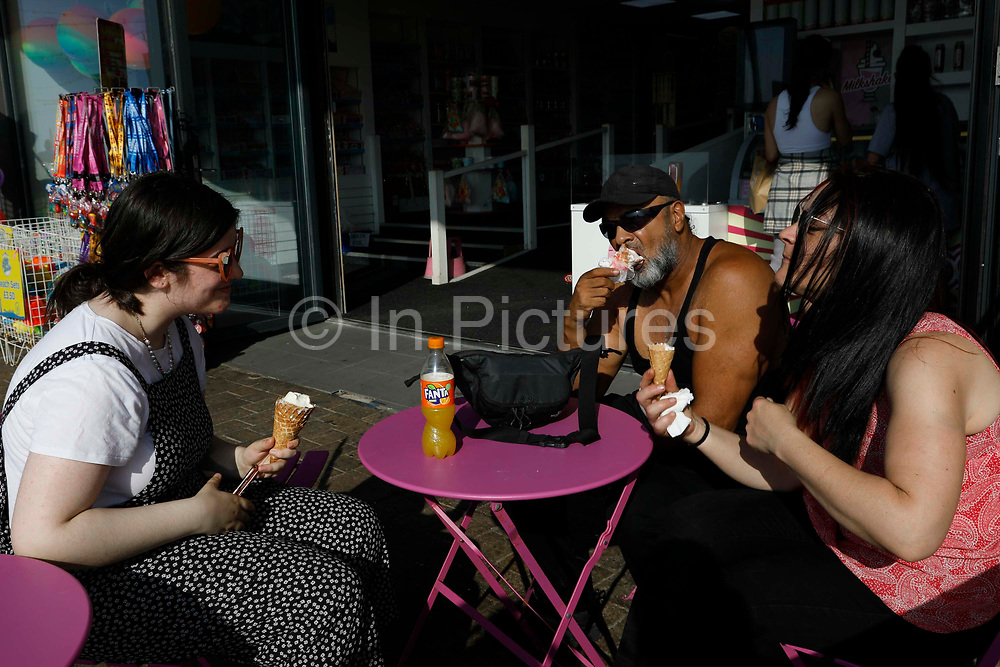 A family of three enjoying ice creams in the scorching heat as temperatures in the country are expected to soar this week on 7th September, 2021 in Blackpool, United Kingdom. Temperatures in the UK are predicted to soar to highs of 29 degrees celsius, coinciding with a rise in daycation and staycation domestic tourism in the country as a result of Covid-19 precautions that make foreign travel increasingly costly and difficult.