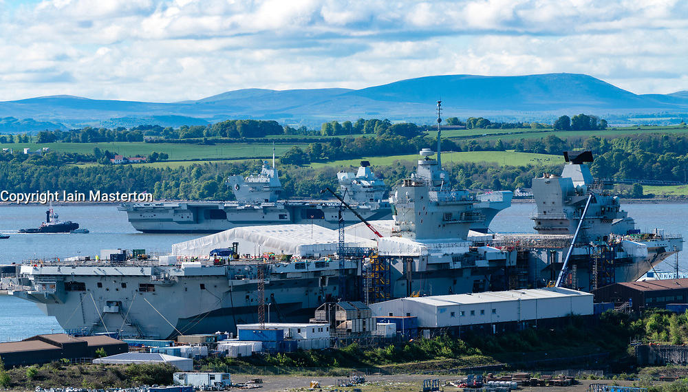 Rosyth ,Scotland, UK. 22 May 2019. Aircraft carrier HMS Queen Elizabeth moored off Rosyth in the River Forth after leaving dry dock yesterday after a visit to her home port. She will leave the Forth today and return to sea in preparation for Westlant 19 deployment which is designed to focus on the operations of her F-35 fighter aircraft. Pictured; Rare view of both of the Royal Navy's aircraft carriers. HMS Queen Elizabeth and in foreground  HMS Prince of Wales still under construction in shipyard at Rosyth.