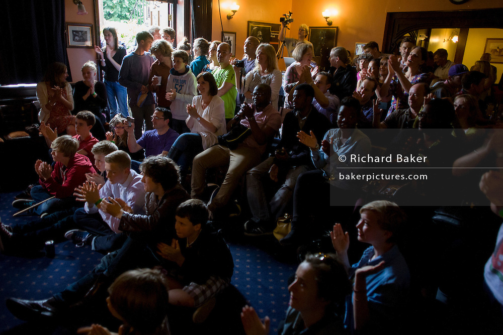 Parents and relatives watch a teenage band perform live in a south London pub.