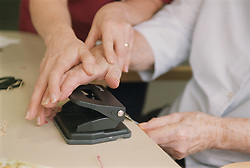 Clinic assistant showing elderly woman how to use a hole punch to make Christmas cards,