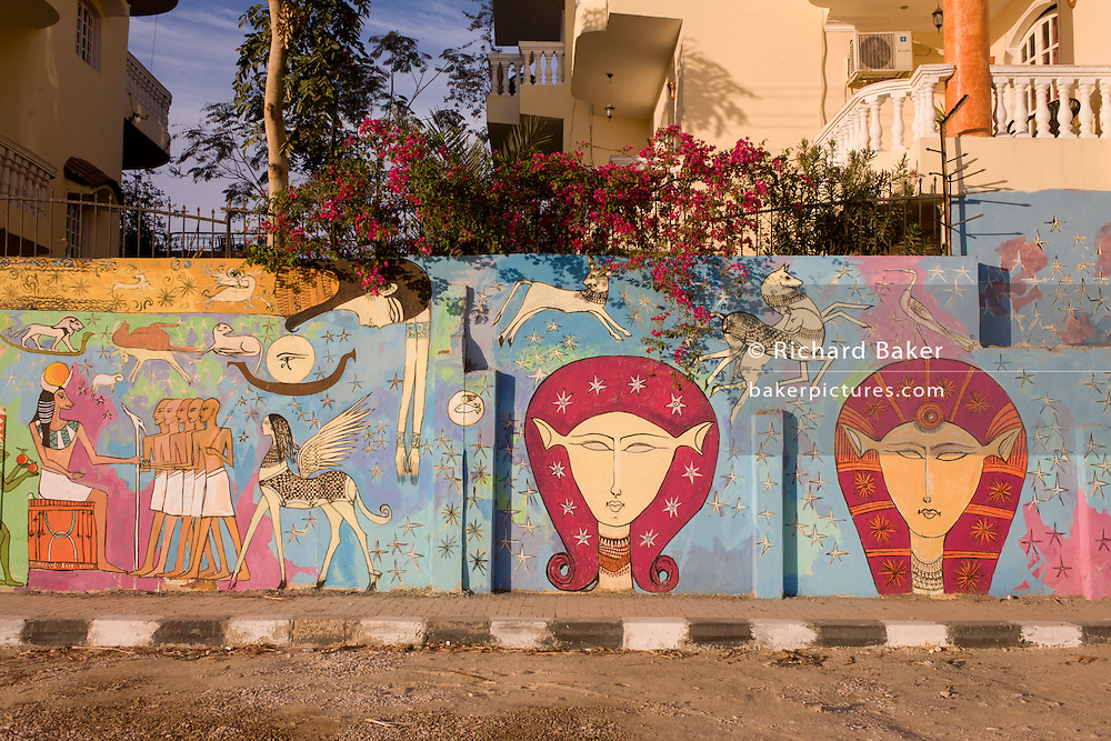 Flowering Bougainvillea and modern hieroglyphic artwork painted on a wall of local wasteground in the village of Gezirat on the West Bank of Luxor, Nile Valley, Egypt.