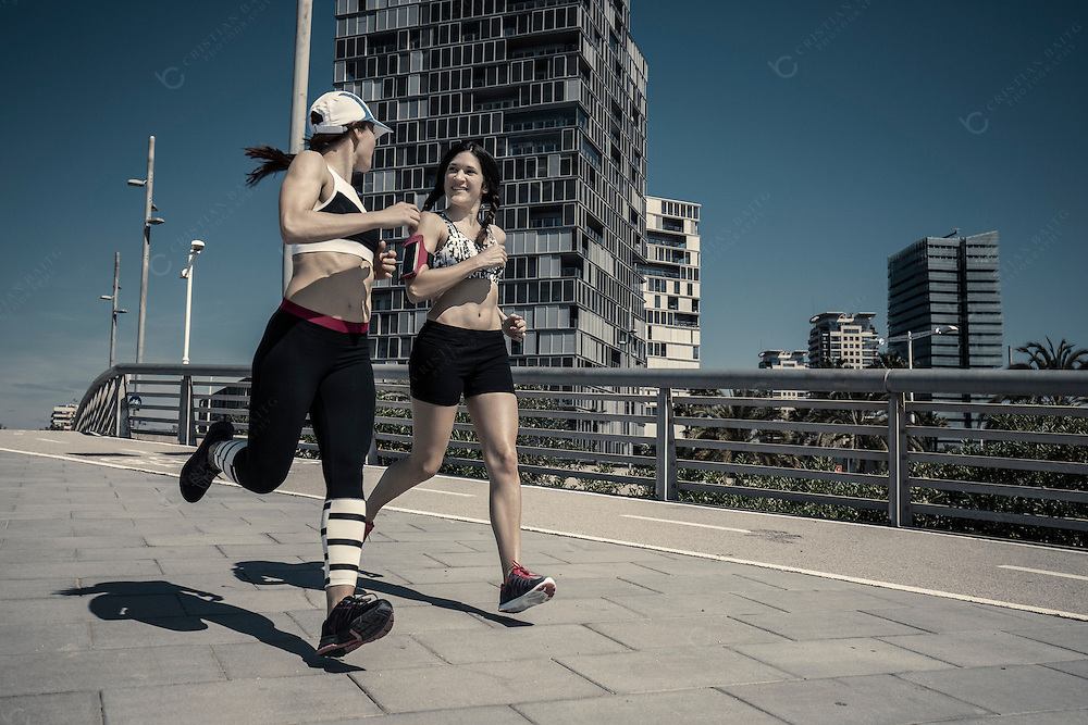 Two women running in the city