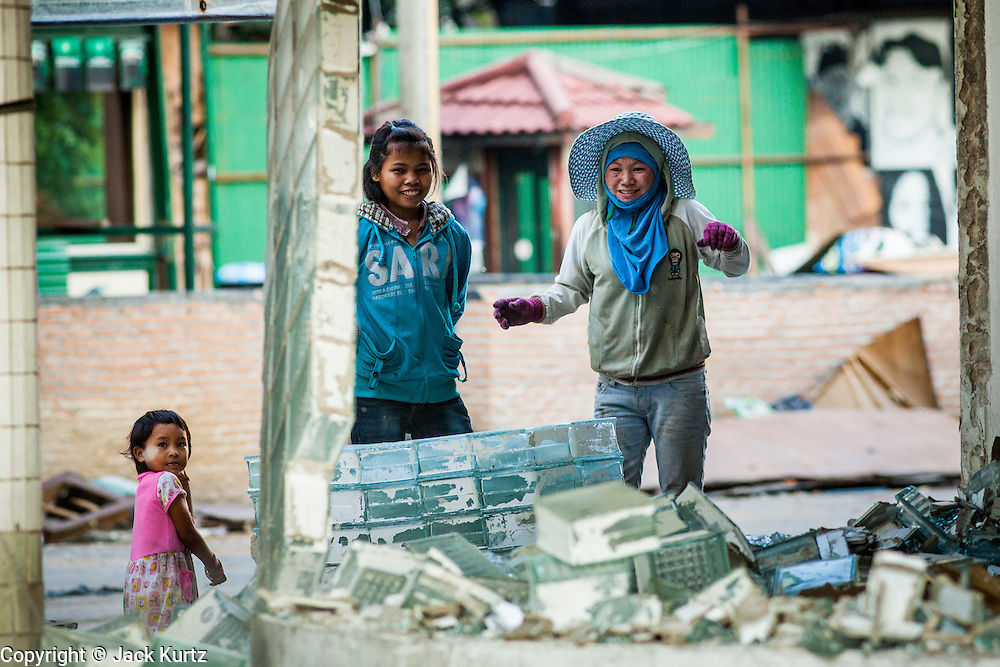"""13 DECEMBER 2012 - BANGKOK, THAILAND:  Women who scavenge glass blocks watch a glass block wall collapse during the demolition of a building  at """"Washington Square"""" a notorious entertainment district off Sukhumvit Soi 22 in Bangkok. Demolition workers on many projects in Thailand live on their job site tearing down the building and recycling what can recycled as they do so until the site is no longer inhabitable. They sleep on the floors in the buildings or sometimes in tents, cooking on gas or charcoal stoves working from morning till dark. Sometimes families live and work together, other times just men. Washington Square was one of Bangkok's oldest red light districts. It was closed early 2012 and is being torn down to make way for redevelopment.    PHOTO BY JACK KURTZ"""