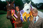 Two young 1990s girls stand with their beloved ponies at a gymkhana in, on 17th September 1999, in Cheltenham, Gloucestershire, England. The word gymkhana is an Indian Raj term which originally referred to a place where sporting events took place and referred to any of various meets at which contests were held to test the skill of the competitors. In the UK and east coast of the US, the term gymkhana now almost always refers to an equestrian event for riders on horses, often with the emphasis on childrens participation such as those organised here by the Pony Club. Gymkhana classes include timed speed events such as barrel racing, keyhole, keg race also known as down and back, flag race, and pole bending.
