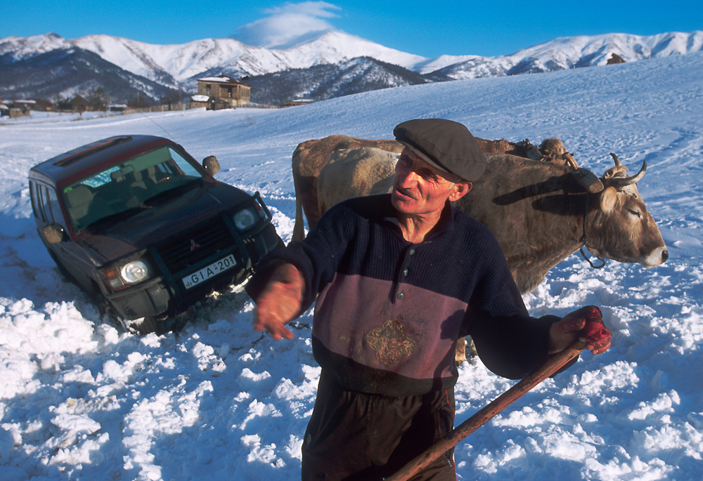 Greek villager assisting to pull vehicle from snow, Greek village, western part of The Country of Georgia