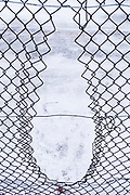 A chain link fence has been cut to allow younger park-users entry through its aperture and into a snow-covered basketball court area in Ruskin Park, on 8th February 2021, in south London, England.