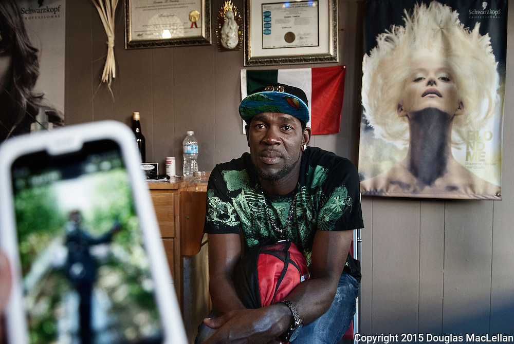 Jonathon Queensborough, a 39 year old Jamaican worker, talks about his daughter back home while waiting for a haircut at Makayla Beauty Salon and Barber Shop in Leamington.