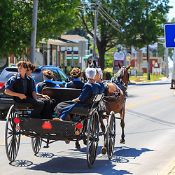 Intercourse, PA - June 12, 2016: Amish youth ride in an open wagon on the Old Philadelphia Pike in Lancaster County, PA.